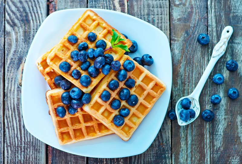 Waffles with blueberry toping and maple syrup